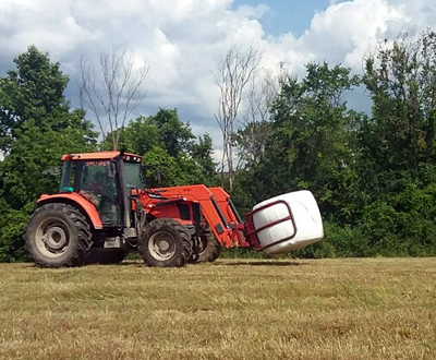 tractor transporting wrapped bale of hay