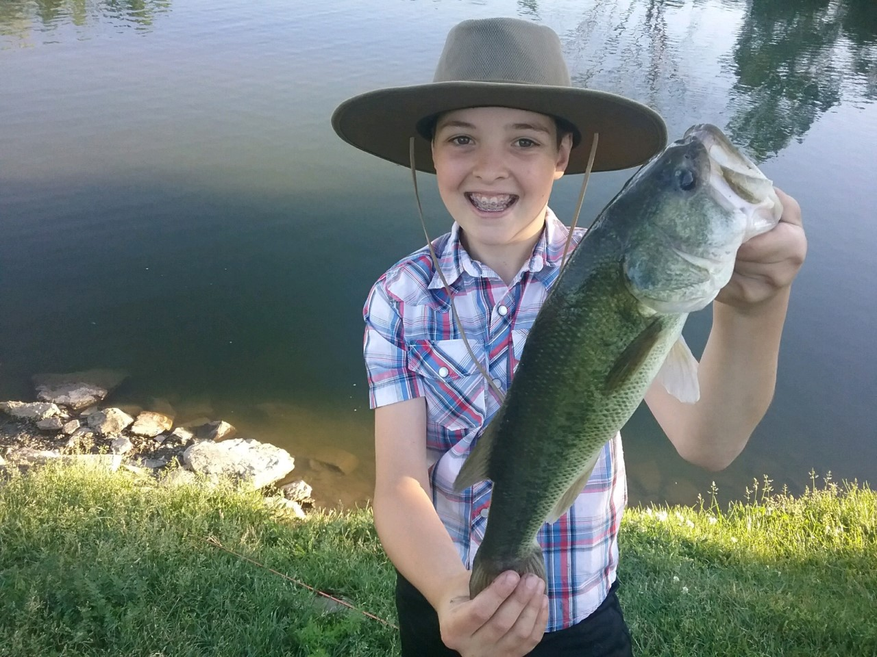Joseph Happy shows off his fish caught in Simply Grazin' owner, Mark Faille's pond in Upstate NY