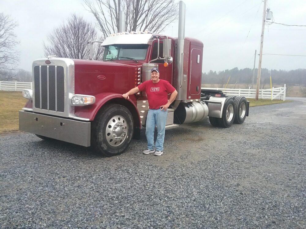 Simply Haulin' driver, Pete Guay, standing with our new 2022 Peterbilt