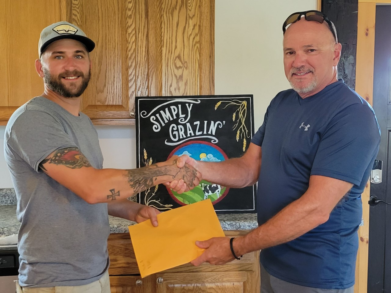 Mark Faille hands Nick Geraghty over the funds raised via the golf tournament to benefit Nick and his family